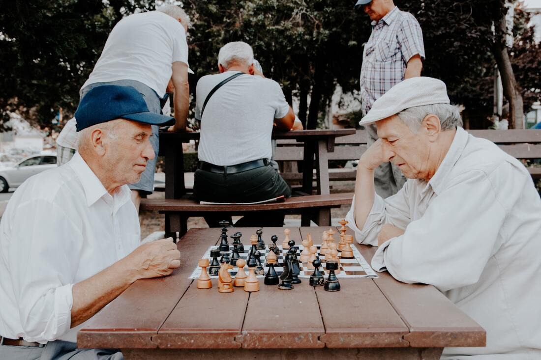 Two older people playing chess together.